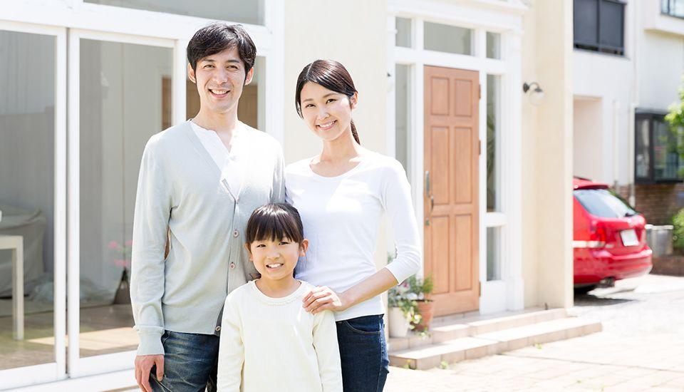 家の前で撮影する家族